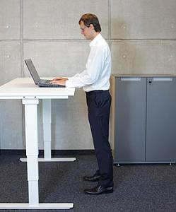 Abbildung: Mann steht am Arbeitspult