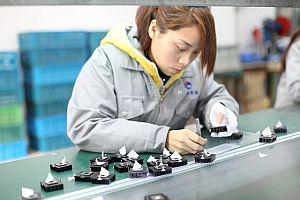Frau arbeitet im Stehen am Fließband