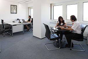 Abbildung: Sitzende Mitarbeiter an ihren Schreibtischen