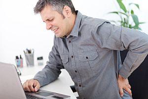 Mann mit Rückenschmerzen an seinem Arbeitsplatz