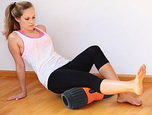 Frau trainiert ihre Unterschenkel mit der ergonomischen Black Roll